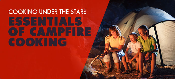 Essentials of Campfire Cooking - a family looking at a campfire at night and smiling - A tent is in the background